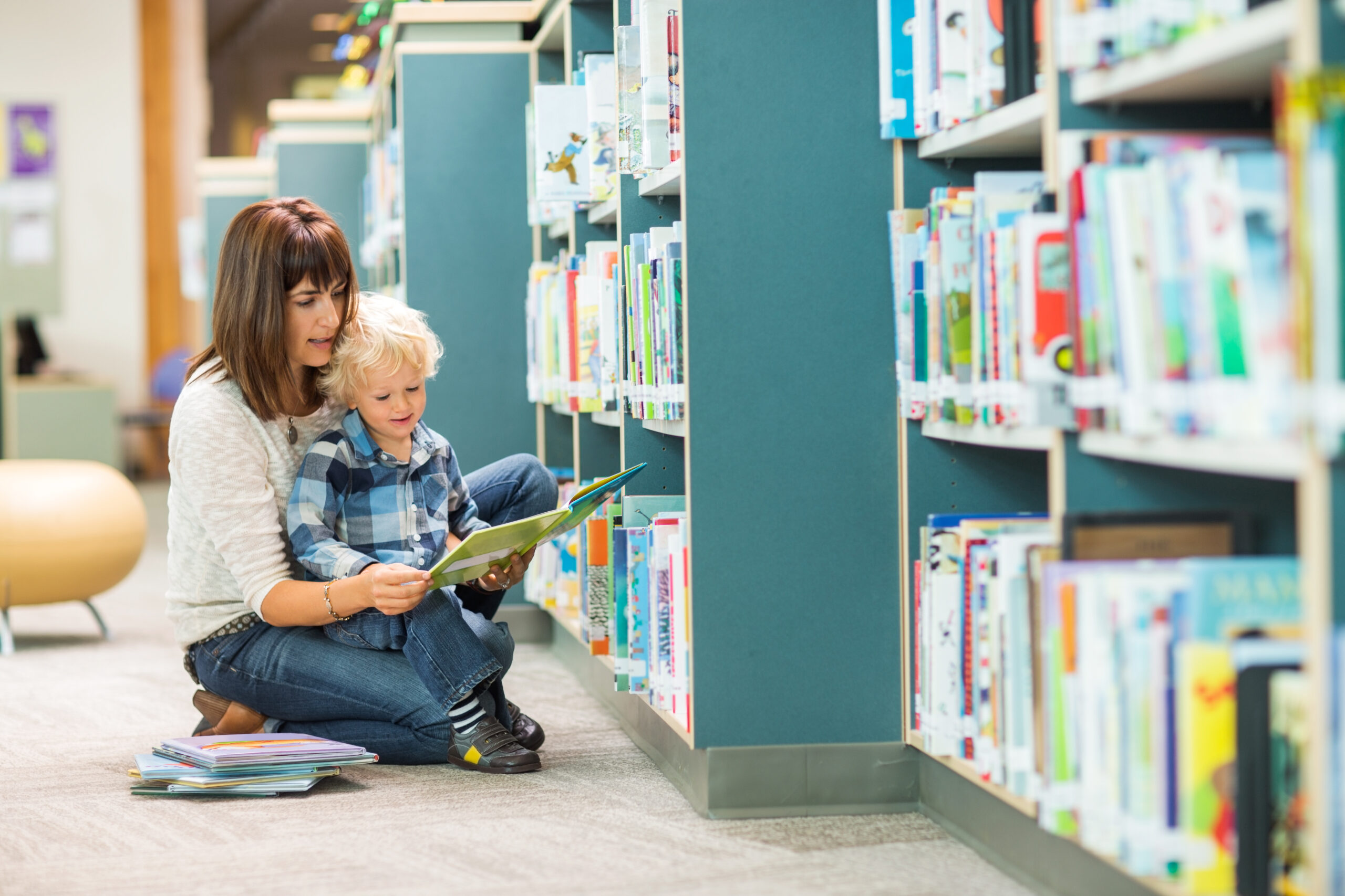 Mother and child reading books in a library setting