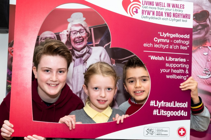 Children in a cardboard photo frame to promote the Living Well scheme