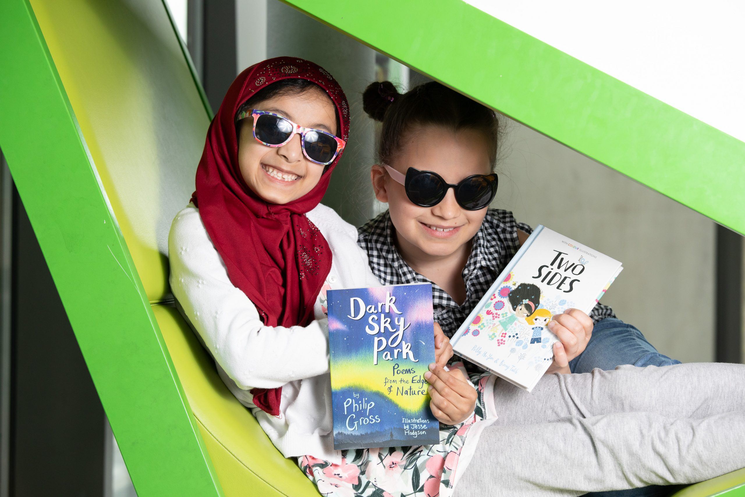 Two girls wearing sunglasses reading books